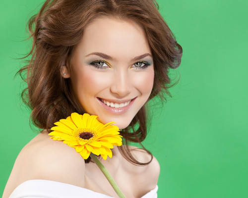 closeup portrait of attractive  caucasian smiling woman brunette studio shot lips toothy smile face hair head and shoulders looking at camera tooth skin makeup yellow flower